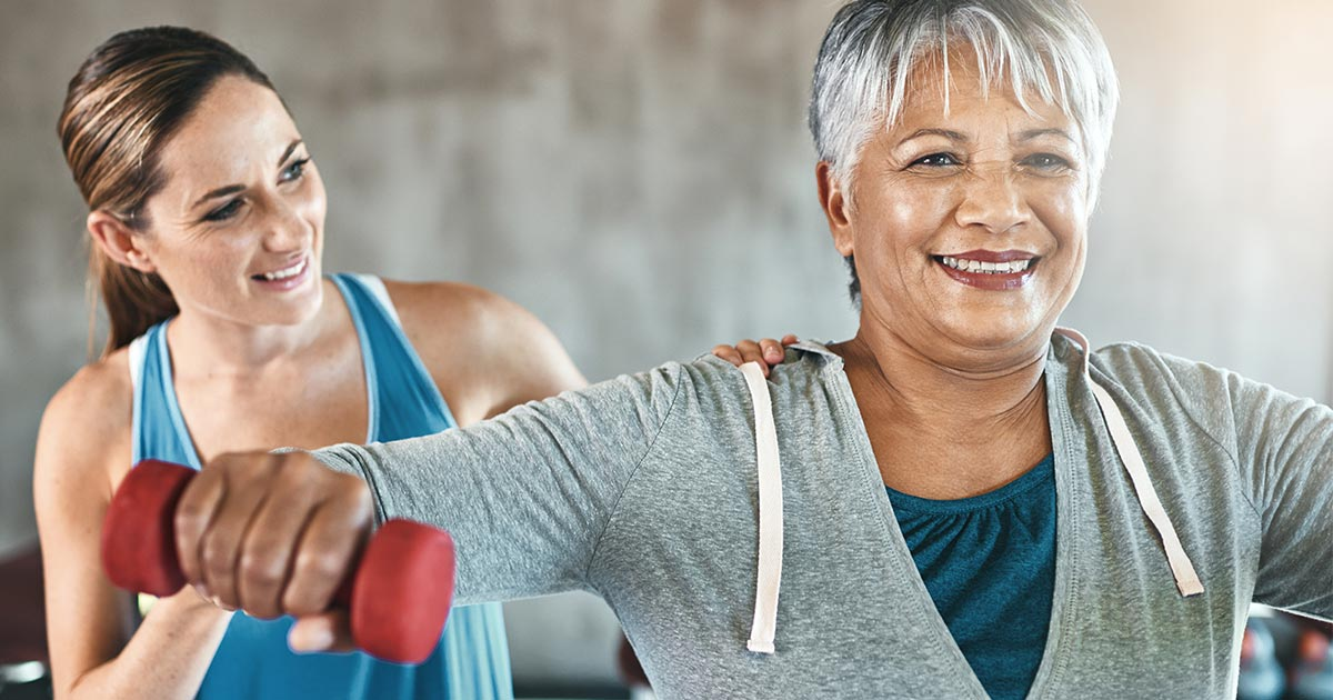 Older woman holding weights and being assisted by physical therapist