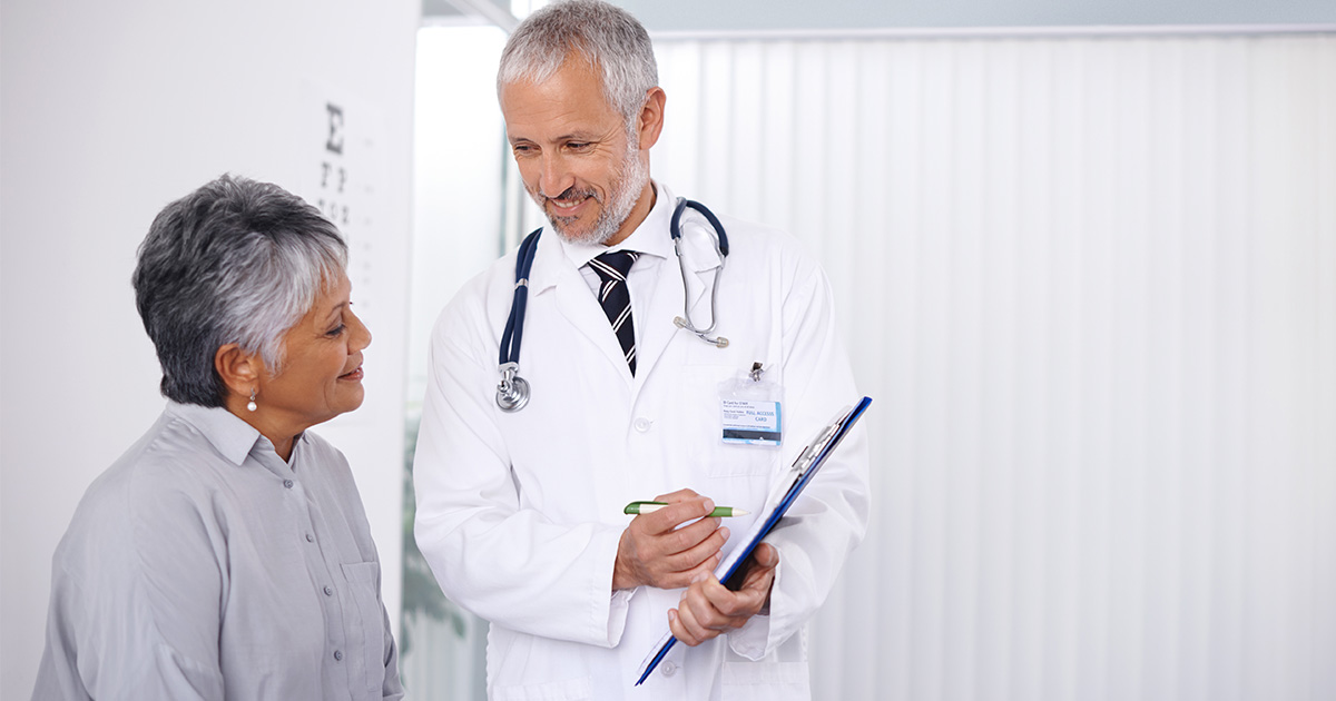 Doctor holding clipboard and speaking with patient