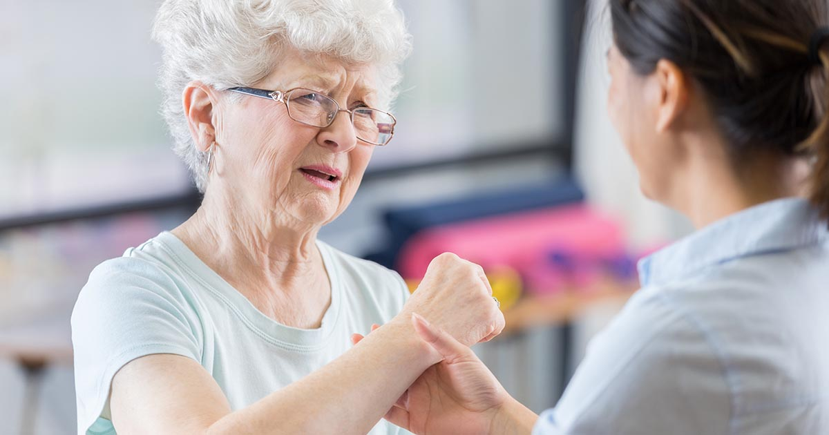 Older woman complaining about wrist pain to physical therapist