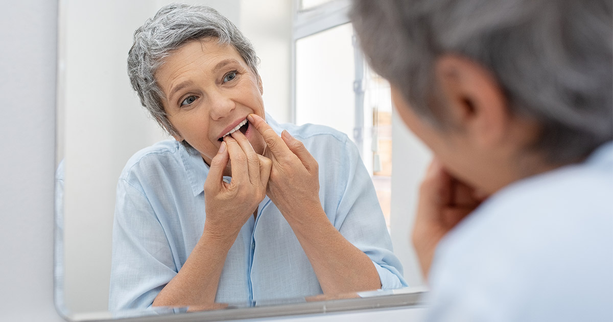 Older woman checking teeth in the mirror