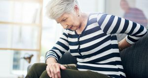 Older woman sitting on couch, holding lower back
