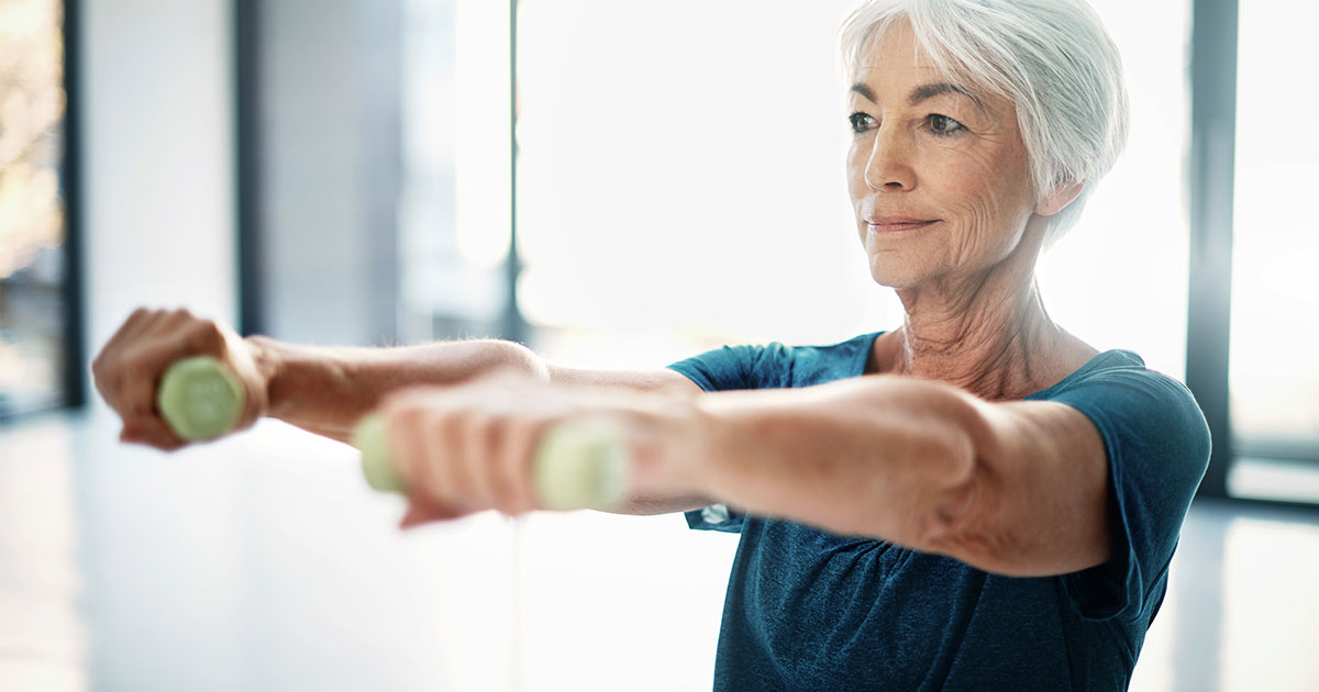 Older woman holding weights out in front of shoulders