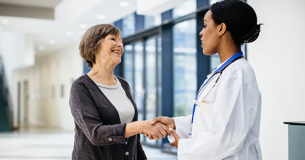 Older woman shaking hands with doctor