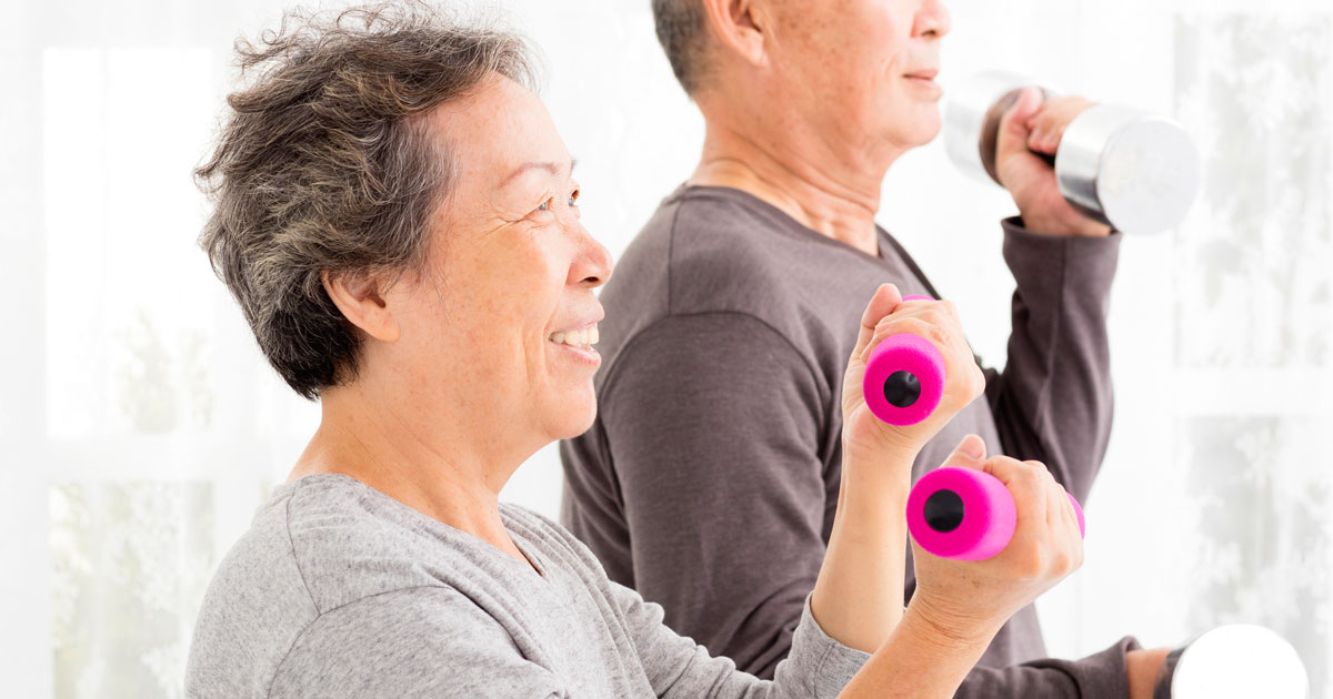 Two older people working out with weights
