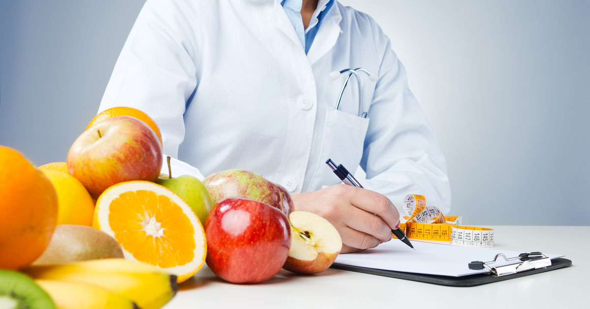 Doctor writing on clipboard with fruit on table