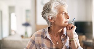 Older woman looking thoughtful with pen held to chin