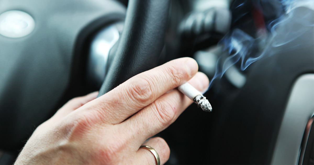 Someone holding cigarette between fingers as they drive