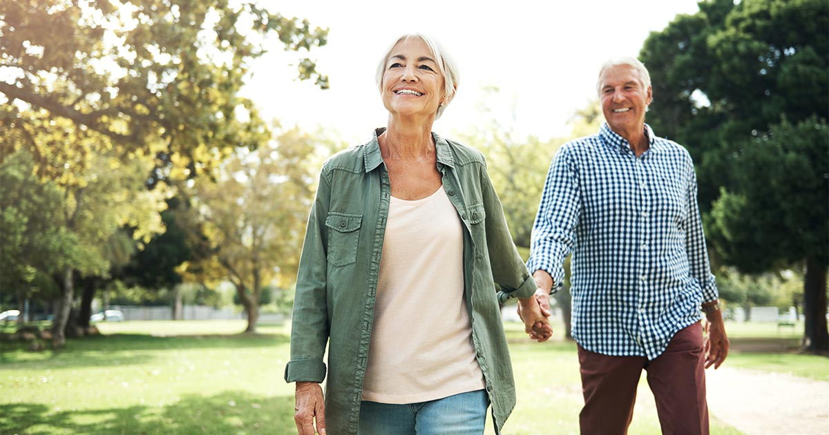Older man and woman holding hands as they walk outside