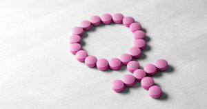 Pink pills in shape of female symbol