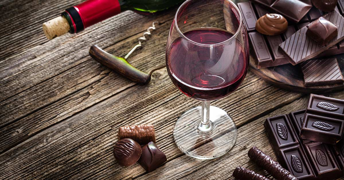 Glass of wine with chocolate and wine bottle