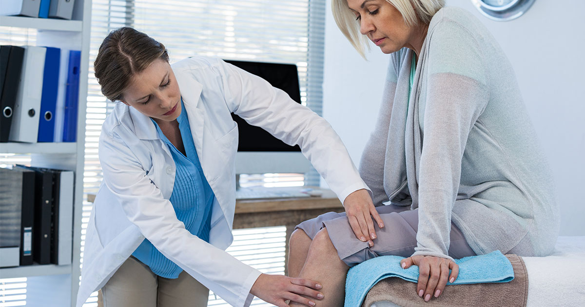 Older woman having her leg checked out by female doctor