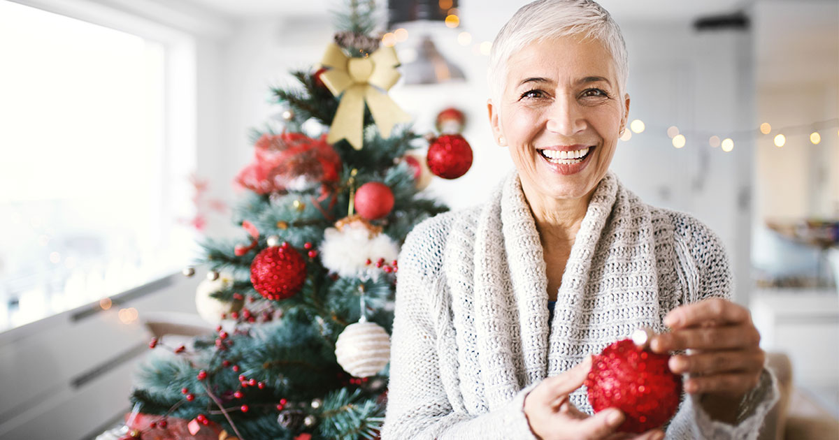 Older woman holding Christmas ornament with Christmas tree in background