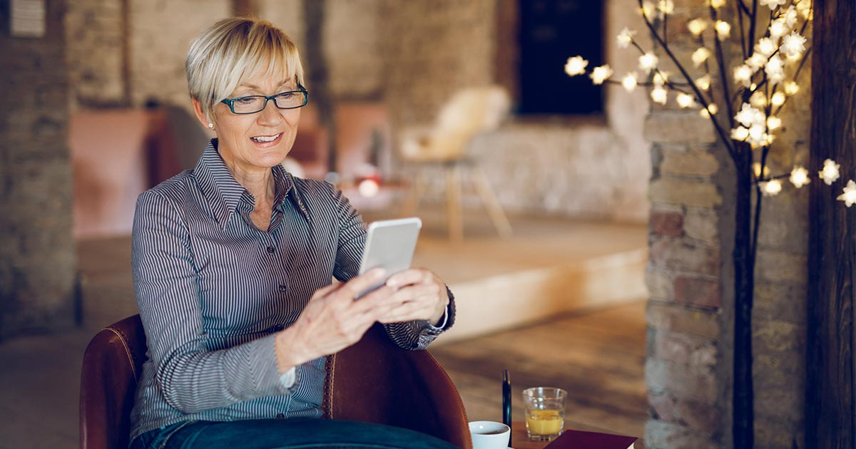 Older woman looking at her phone while sitting in living room
