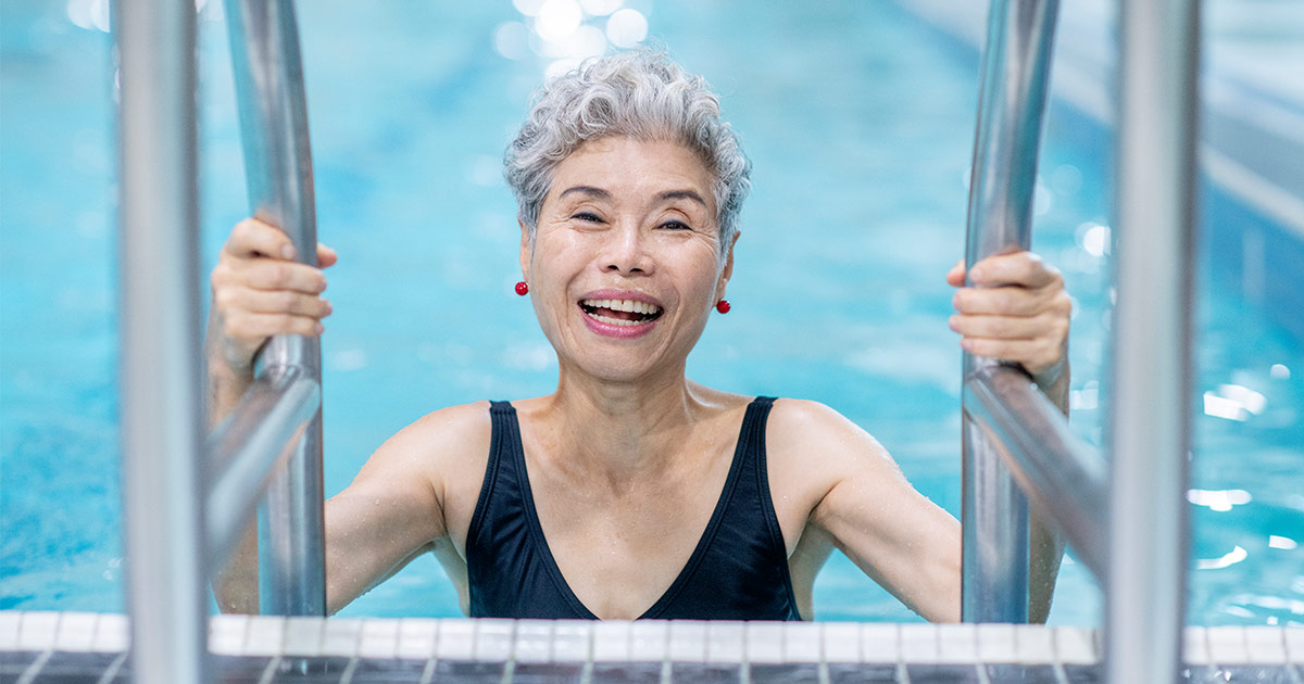 Older woman standing on ladder in the pool