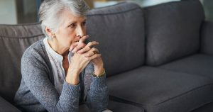 Woman sitting on couch looking anxious