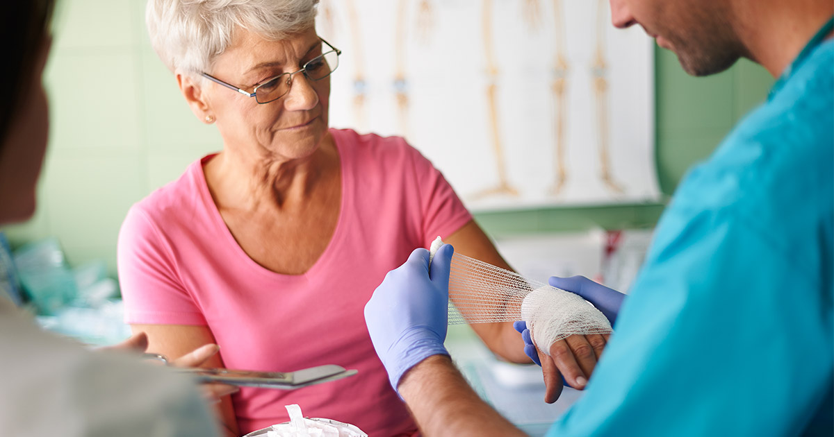 Older woman having her hand wrapped by a doctor