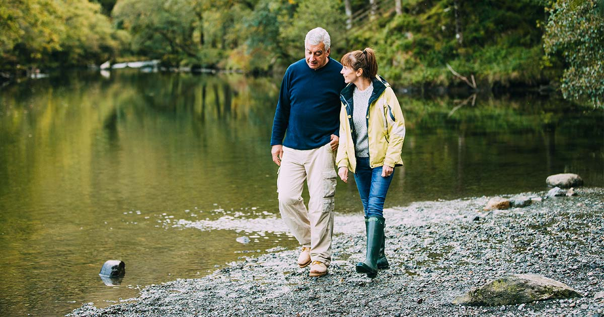 Two older people walking by the water