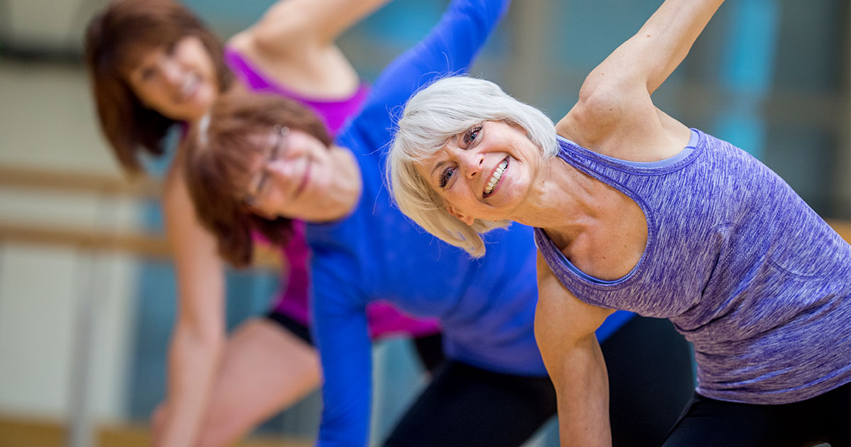 Three older woman stretching