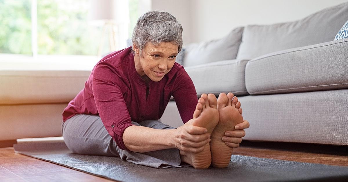Older woman on yoga match stretching