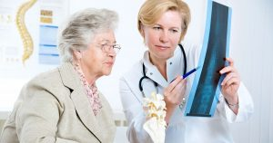 Older woman being shown x-ray chart by doctor