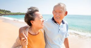 Older man and woman on the beach with arms around each other