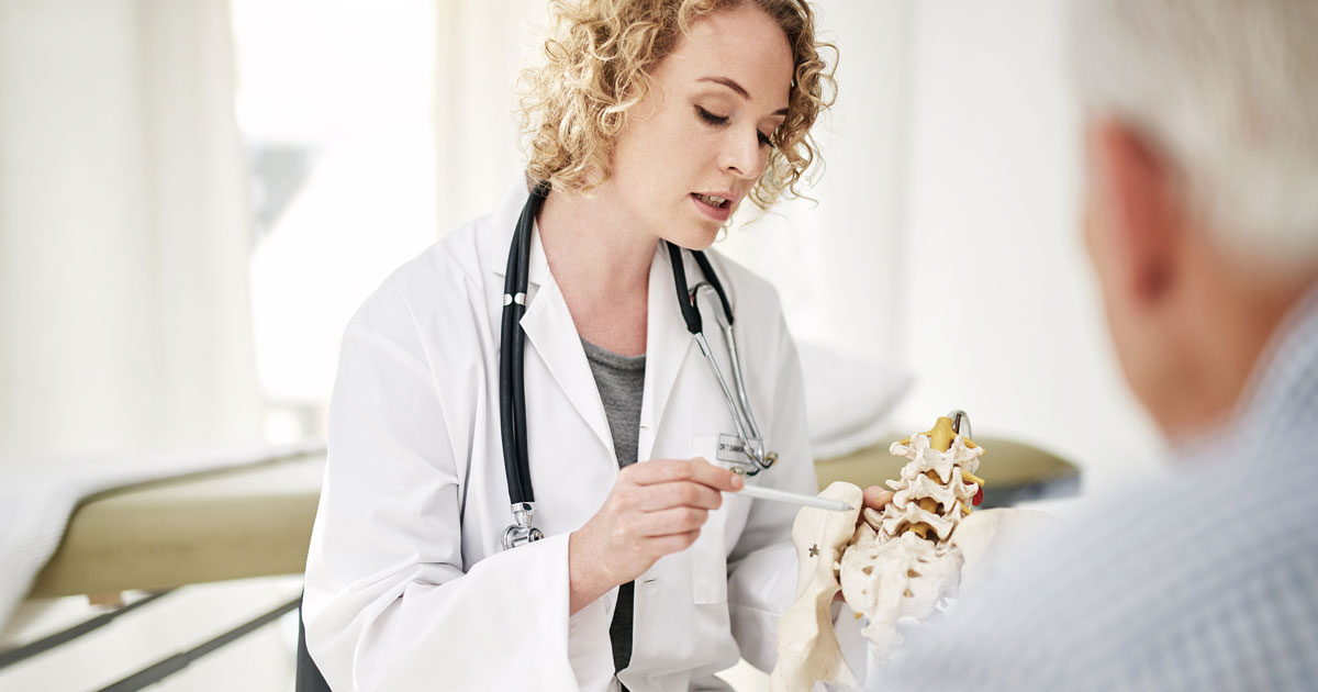 Doctor pointing to part of a model of a skeleton while patient watches