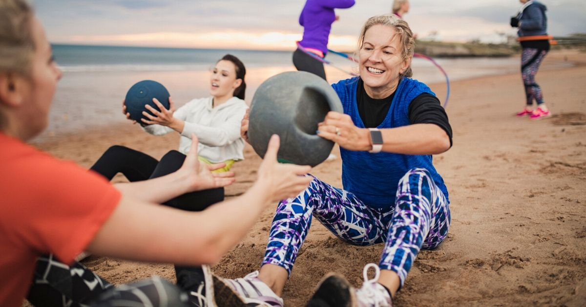 senior women exercising on the beach