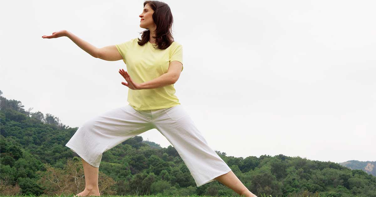 a woman practicing tai chi outside, an example of an osteoporosis safety tip